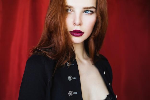 Schönes rothaariges mädchen in der schwarzen aufgeknöpften jacke mit den roten lippen auf dem roten hintergrund, der weg schaut. modefotografie. helles aussehen. rote haare.