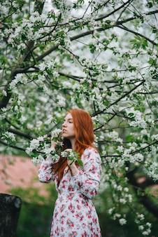 Schönes rothaariges mädchen in einem weißen kleid unter blühenden apfelbäumen im garten.