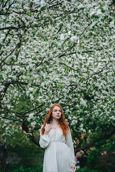 Schönes rothaariges mädchen in einem weißen kleid unter blühenden apfelbäumen im garten