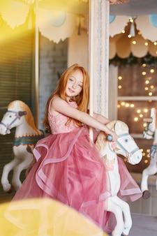 Schönes rothaariges mädchen mit dem langen haar und den blauen augen reitet ein karussell in einem langen rosa kleid. karussell in form von pferden, feiert rothaarige frau ihren geburtstag im vergnügungspark