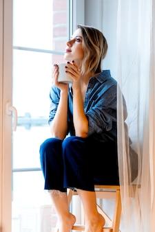 Schönes rothaariges mädchen mit der warmen tasse kaffee, die auf hölzernen treppen zu hause sitzt und in fenster schaut