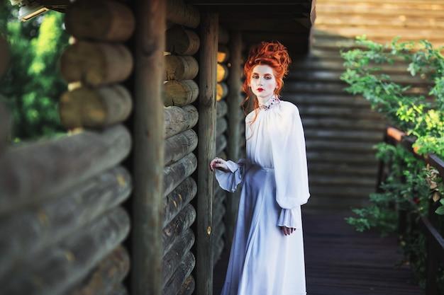Schönes rothaariges mädchen mit einem hohen haar in einem alten weißen kleid im park. die viktorianische ära. historisches kostüm. weiße königin. prinzessin schloss