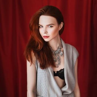 Schönes rothaariges mädchen mit einer halskette um ihren hals mit roten lippen auf rotem hintergrund, der die kamera betrachtet. modefotografie. helles aussehen. rote haare. porträt im gesicht