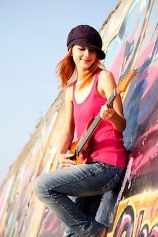 Schönes rothaariges mädchen mit gitarren- und graffitiwand am hintergrund.