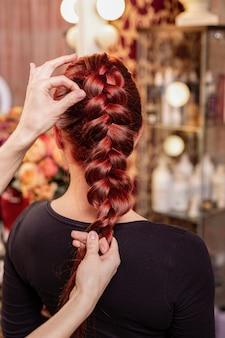 Schönes, rothaariges mädchen mit langen haaren, friseur spinnt ein französisches geflecht, in einem schönheitssalon.