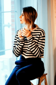 Schönes rothaariges mädchen mit tasse kaffee ch sitzt auf kleinen treppen zu hause nahe fenster.