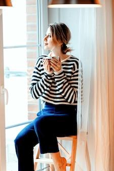 Schönes rothaariges mädchen mit tasse kaffee sitzt auf kleinen treppen zu hause nahe fenster.