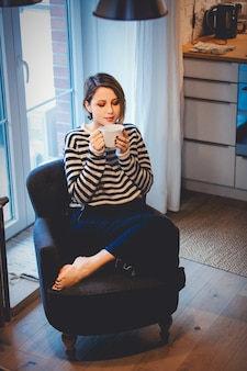 Schönes rothaariges mädchen mit tasse kaffee sitzt im sessel zu hause nahe fenster.