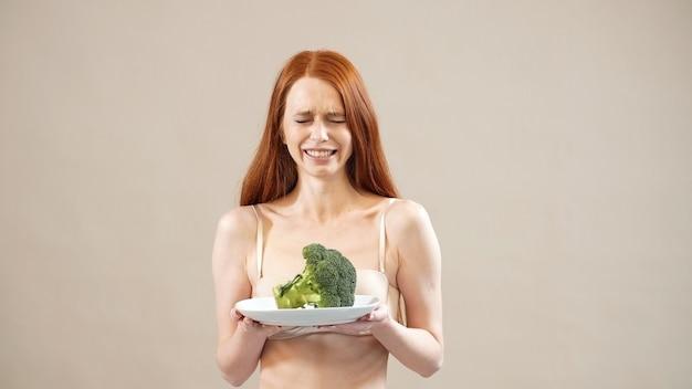 Schönes rothaariges mädchen mit verärgertem gesicht, das brokkoli in einem teller hält, angst vor übergewicht, magersucht