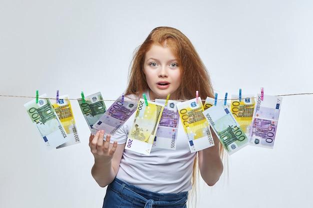 Schönes rothaariges mädchen trocknet euro-banknoten, die an einem seil hängen