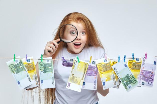 Schönes rothaariges mädchen untersucht euro-banknoten durch eine lupe.
