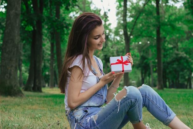 Schönes sanftes mädchen sitzt im park auf dem gras und hält ein geschenk
