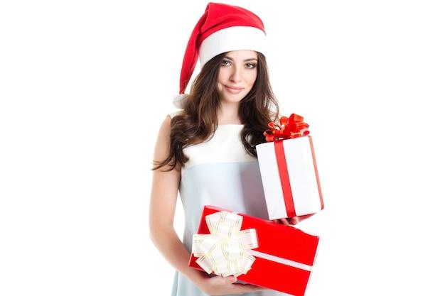 Schönes santa girl isoliert. lächelnde frau, die im studio mit geschenken aufwirft.