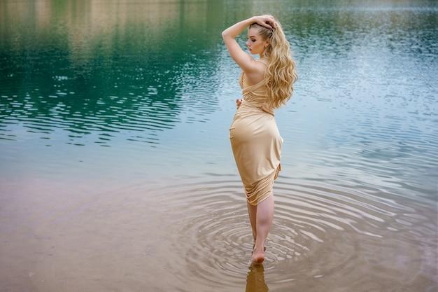 Schönes schlankes mädchen mit dem langen haar, das im wasser stehend aufwirft.