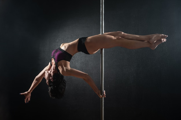 Schönes schlankes mädchen mit pylon. weibliche stangentänzerin, die auf einem schwarzen hintergrund tanzt