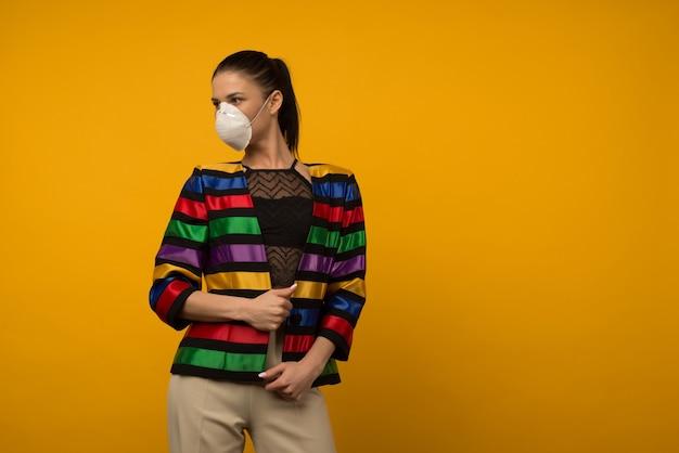 Schönes schlankes mädchenmodemodell, das in einem schützenden atemschutzgerät auf gelbem hintergrund aufwirft. regenbogenfarbene jacke der lgbt-gemeinschaft