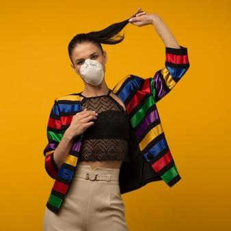 Schönes schlankes mädchenmodemodell, das in einem schützenden atemschutzgerät auf gelbem raum aufwirft. regenbogenfarbene jacke der lgbt-gemeinschaft