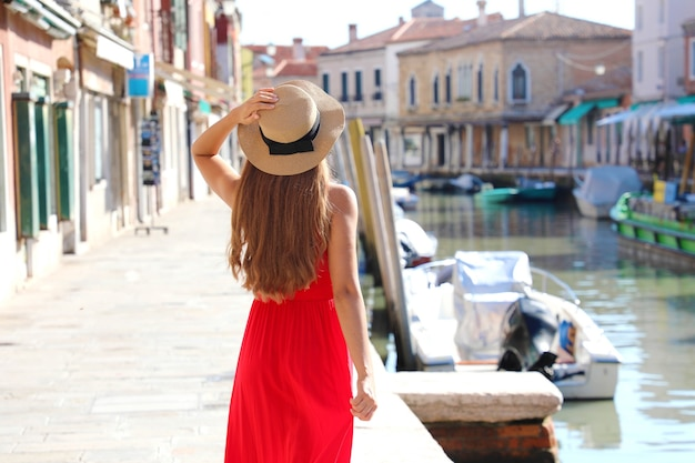 Schönes schlankes modell mit rotem kleid und hut zu fuß in murano, venedig