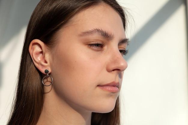 Schönes schmuckmodell in modernen silbernen runden minimalohrringen