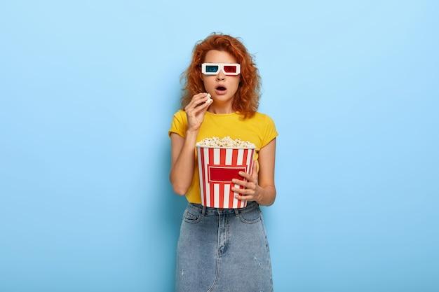 Schönes schockiertes ingwer charmantes mädchen hält eimer mit popcorn
