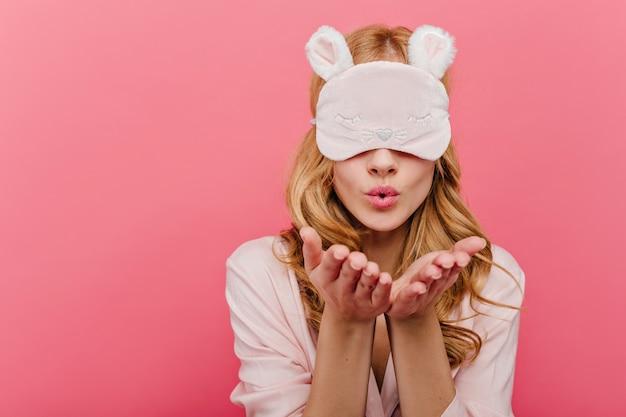 Schönes schüchternes mädchen mit den blonden haaren, die in der schlafmaske aufwerfen. innenaufnahme des entzückenden kaukasischen weiblichen modells sendet luftkuss in augenmaske.
