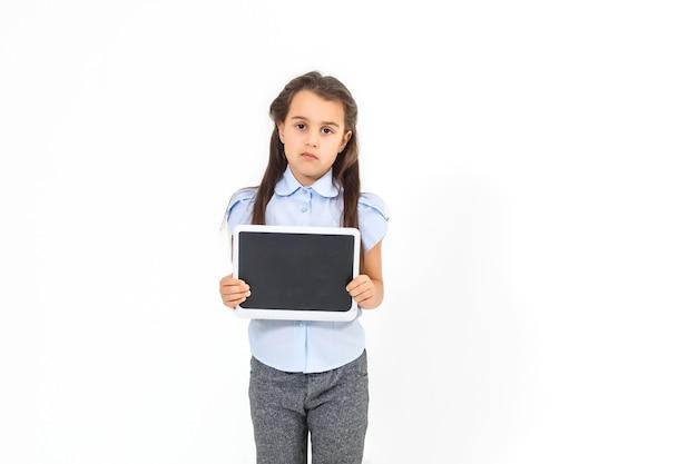 Schönes schulmädchen in einem business-anzug, das ein tablet in den händen hält und in die kamera schaut, selektiver fokus auf das tablet