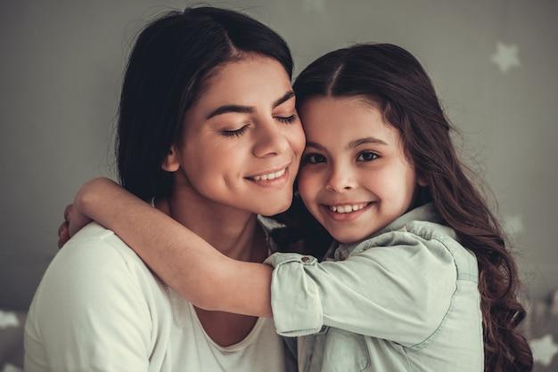 Schönes schulmädchen und ihre mutter umarmen und lächeln.