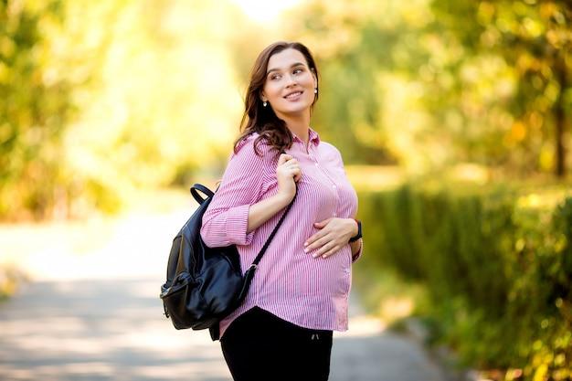 Schönes schwangeres mädchen auf einem sommerspaziergang