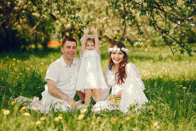Schönes schwangeres mädchen in einem langen weißen kleid mit ihrem freund und ihrer kleinen tochter