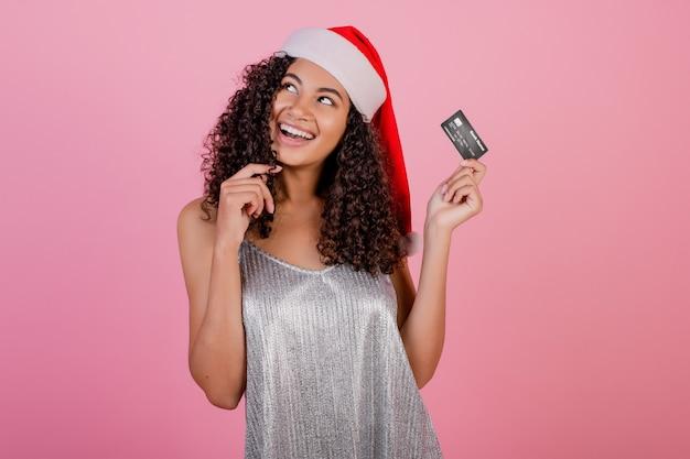 Schönes schwarzes mädchen mit der kreditkarte, die feiertag sankt-hut trägt