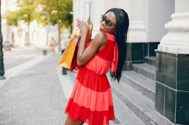 Schönes schwarzes mädchen mit einkaufstüten in einer stadt