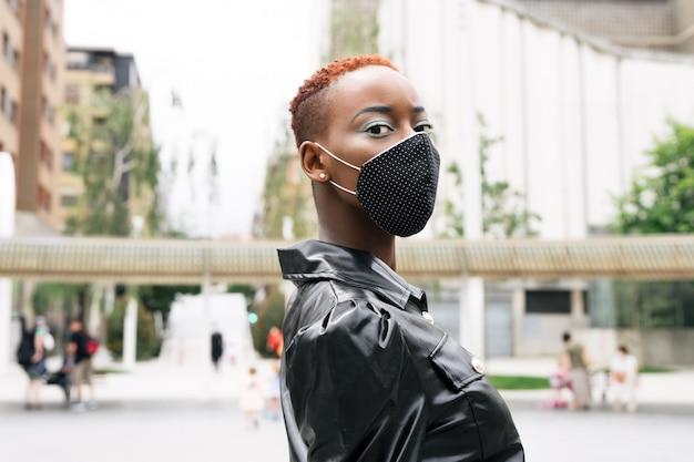 Schönes schwarzes mädchenmodell mit maske aufgrund der coronavirus-pandemie covid 19, die mit einem schönen schwarzen kleid stilvoll auf der straße geht