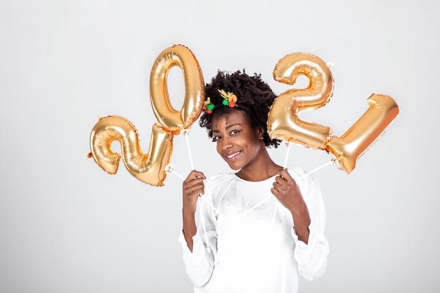 Schönes schwarzes partygirl mit lockigem haar und festlichen kleidern, die auf studiohintergrund aufwerfen und goldballons halten