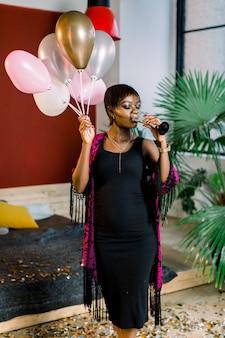 Schönes schwarzes weibliches modell mit luftballons und einem glas champagner, die für geburtstagsfeier vorbereiten. raffiniertes afrikanisches mädchen im schwarzen kleid, das mit lächeln nach ereignis bleibt.
