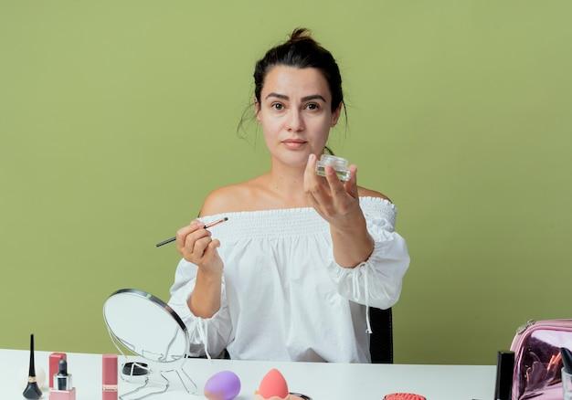 Schönes selbstbewusstes mädchen sitzt am tisch mit make-up-werkzeugen, die make-up-pinsel und lidschattenpalette lokalisiert auf grüner wand halten