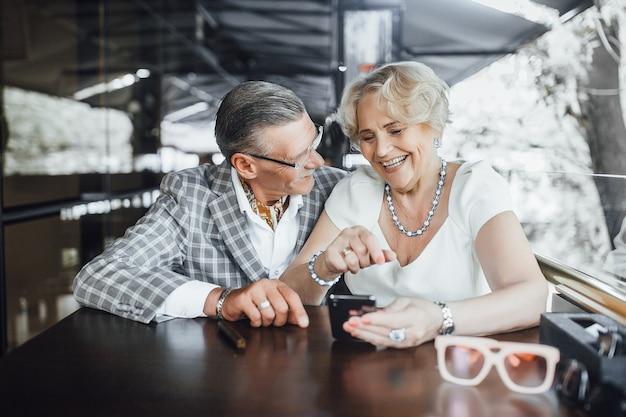 Schönes seniorenpaar, das etwas am telefon sucht, das in der sommerterrasse im modernen café sitzt und aufrichtig lächelt