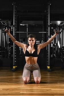 Schönes sexy athletisches junges kaukasisches mädchen, das in der turnhalle trainiert. brustmuskeln mit hanteln aufpumpen