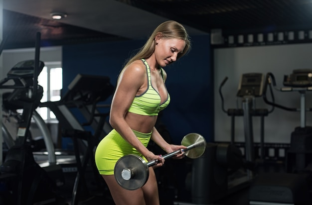Schönes sexy athletisches muskulöses junges mädchen. eignungsmädchen bildet in der turnhalle aus und tut übungen mit einem barbell