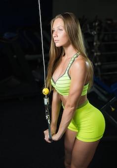 Schönes sexy athletisches muskulöses junges mädchen. kaukasische eignungsmädchenzüge in der turnhalle