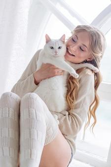 Schönes sexy blondes sitzen mit der katze