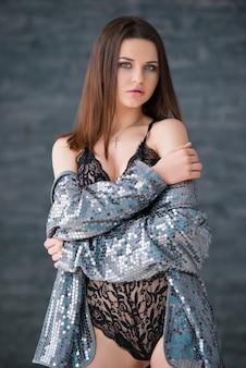 Schönes sexy brünettes mädchen im schwarzen spitzenanzug und in der silbernen jacke steht gegen den grauen backsteinmauerhintergrund.