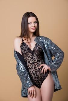 Schönes sexy brünettes mädchen in einem schwarzen spitzenoverall und in der silbernen jacke, die auf einem beigen papierhintergrund im studio stehen.