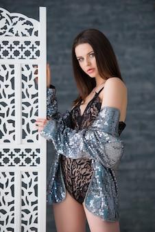 Schönes sexy brünettes mädchen in einem schwarzen spitzenoverall und in der silbernen jacke steht nahe dem weißen durchbrochenen hölzernen bildschirm.