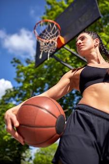 Schönes sexy eignungsmädchen in der schwarzen sportabnutzung mit perfektem körper mit basketball am basketballplatz. sport, fitness, lifestyle-konzept
