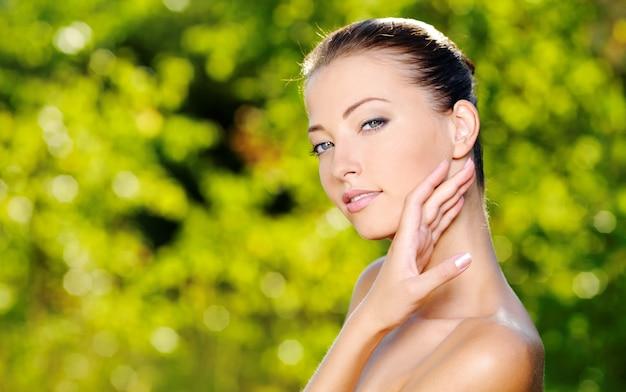 Schönes sexy gesicht einer jungen frau mit frischer gesundheitshaut. frau, die auf der natur aufwirft. model streichelte ihren körper.