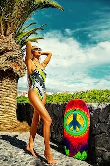 Schönes sexy heißes frauenmodell mit blondem haar im bunten bikini, der am sommerstrand aufwirft