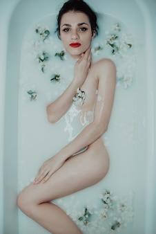 Schönes sexy junges nacktes mädchen genießt und entspannt sich im bad mit milch und apfelblüte für verjüngung
