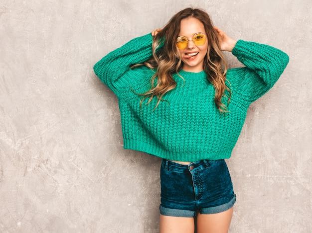Schönes sexy lächelndes herrliches mädchen in der grünen modischen strickjacke. frau, die in der runden sonnenbrille aufwirft. modell, das spaß hat und ihre zunge zeigt