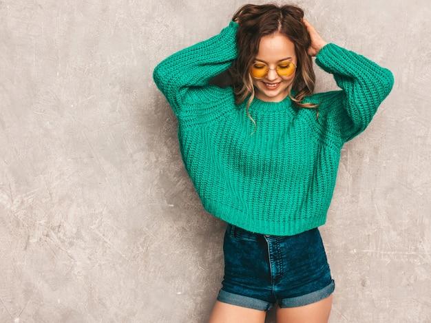 Schönes sexy lächelndes herrliches mädchen in der grünen modischen strickjacke. frau, die in der runden sonnenbrille aufwirft. modell, das spaß hat