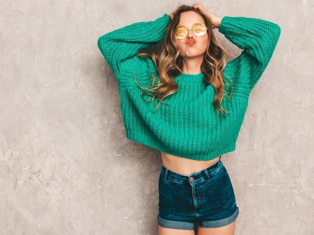 Schönes sexy lächelndes herrliches mädchen in der grünen modischen strickjacke. frau, die in der runden sonnenbrille aufwirft. vorbildlich, spaß habend und kuss gebend